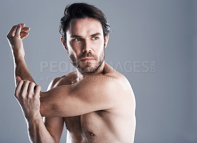 Buy stock photo Studio shot of a handsome young man posing without a shirt against a grey background
