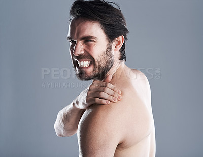 Buy stock photo Studio shot of a handsome young woman wincing in pain against a grey background