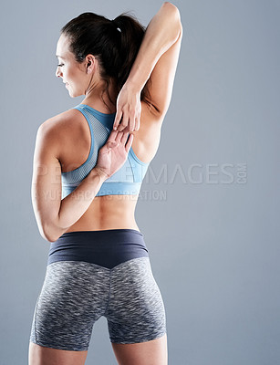 Buy stock photo Studio shot of an attractive young woman doing stretch exercises against a grey background