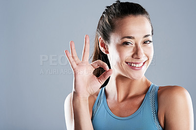 Buy stock photo Studio shot of an attractive young woman showing the okay sign with her hand while standing against a grey background