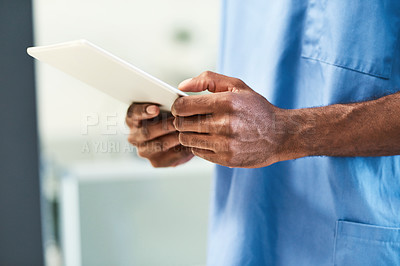 Buy stock photo Closeup shot of a medical practitioner using a digital tablet in a hospital