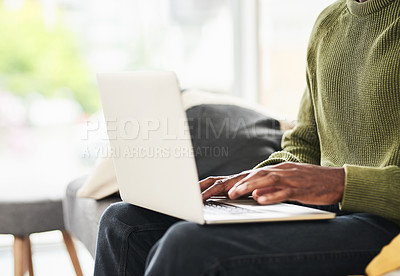 Buy stock photo Cropped shot of an unrecognizable young man using his laptop while chilling on the sofa at home