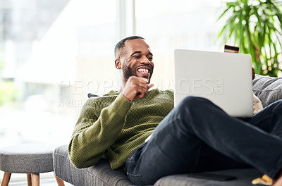 Buy stock photo Cropped shot of a handsome young man using his laptop while chilling on the sofa at home