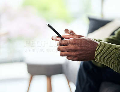 Buy stock photo Cropped shot of an unrecognizable young man using his cellphone while chilling on the sofa at home
