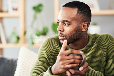 Buy stock photo Cropped shot of a handsome young man looking contemplative while enjoying a cup of coffee on the sofa at home