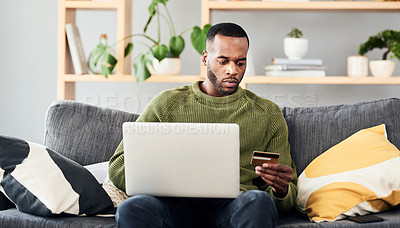 Buy stock photo Cropped shot of a handsome young man shopping online using his laptop while chilling on the sofa at home