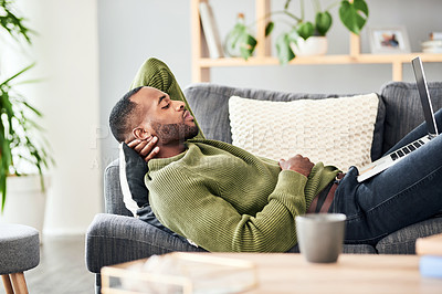 Buy stock photo Cropped shot of a handsome young man taking a nap on his sofa at home