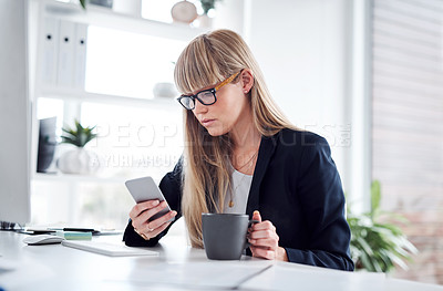 Buy stock photo Shot of an attractive young businesswoman looking concerned while using a cellphone in her office at work