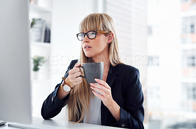 Buy stock photo Shot of an attractive young businesswoman drinking coffee while working on a computer in a modern office
