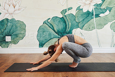 Buy stock photo Shot of a sporty young woman practicing yoga in a studio