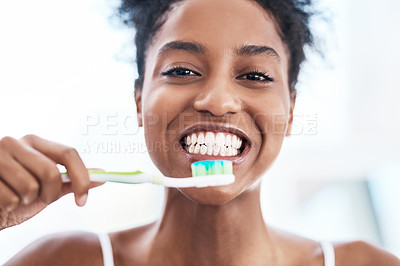 Buy stock photo Portrait of a beautiful young woman brushing her teeth in the bathroom at home