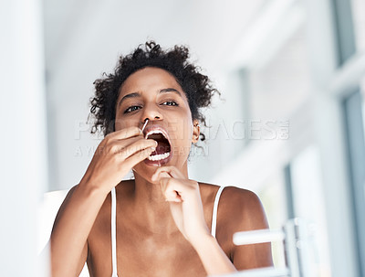 Buy stock photo Shot of a beautiful young woman flossing her teeth in the bathroom at home