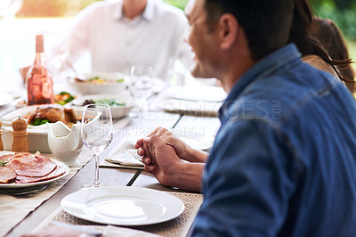 Buy stock photo Cropped shot of an unrecognizable young man holding hands with his family to say grace during lunch outdoors