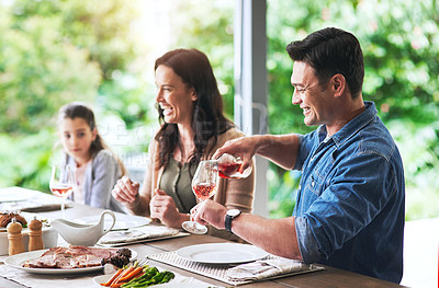 Buy stock photo Shot of a cheerful young man pouring a glass of wine while dining with his family outdoors