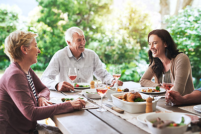 Buy stock photo Cropped shot of an affectionate young woman enjoying lunch with her aged parents outdoors