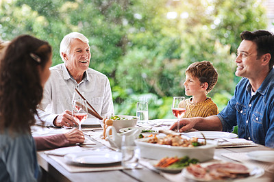 Buy stock photo Cropped shot of a cheerful aged man dining with his family for lunch outdoors