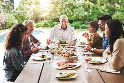 Buy stock photo Cropped shot of an affectionate family enjoying lunch around a table outdoors