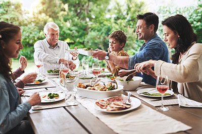 Buy stock photo Cropped shot of a cheerful young man enjoying lunch with his family outdoors
