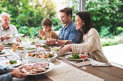 Buy stock photo Cropped shot of a cheerful young woman enjoying lunch with her family outdoors