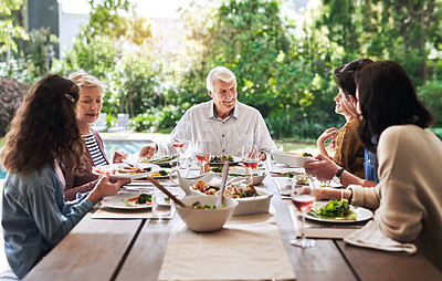 Buy stock photo Cropped shot of a cheerful family enjoying lunch around a table outdoors