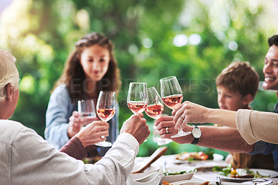 Buy stock photo Cropped shot of a cheerful family making a toast while enjoying lunch outdoors