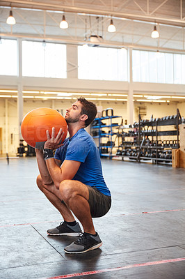 Buy stock photo Full length shot of a handsome young man working out with a medicine ball in the gym