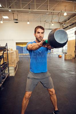 Buy stock photo Cropped shot of a handsome young man working out with a kettle bell in the gym