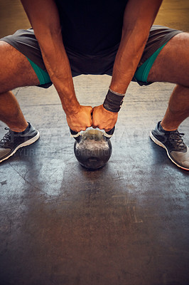Buy stock photo Cropped shot of an unrecognizable young man working out with a kettle bell in the gym