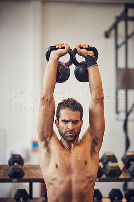 Buy stock photo Cropped shot of a handsome young man working out with kettle bells in the gym