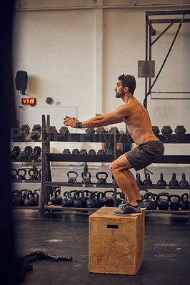 Buy stock photo Full length shot of a handsome young man box jumping while working out in the gym