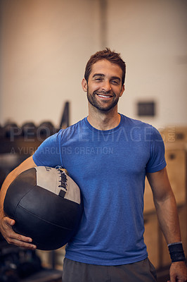 Buy stock photo Cropped portrait of a handsome young man working out with a medicine ball in the gym