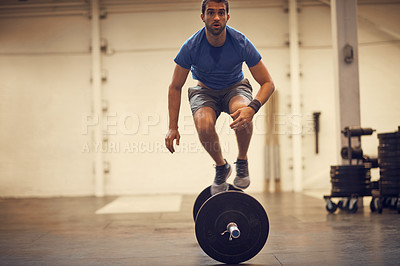 Buy stock photo Full length shot of a handsome young man balancing on a barbell while working out in the gym