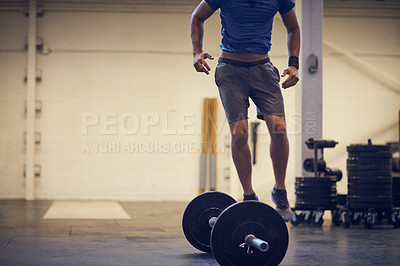 Buy stock photo Full length shot of an unrecognizable young man balancing on a barbell while working out in the gym