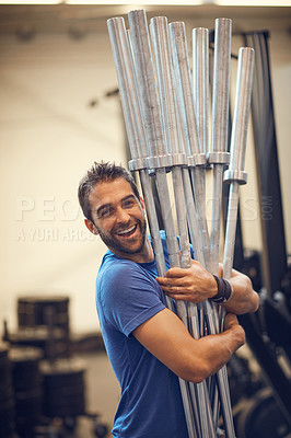Buy stock photo Cropped portrait of a handsome young man carrying equipment while working out in the gym