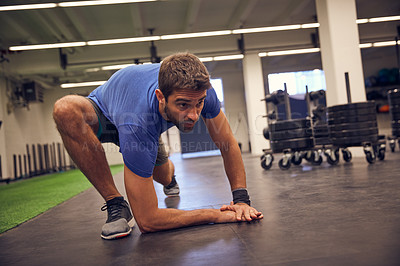 Buy stock photo Full length shot of a handsome young man stretching while working out in the gym
