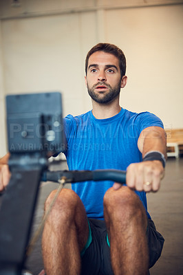 Buy stock photo Cropped shot of a handsome young man working out on a rowing machine in the gym