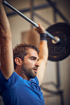 Buy stock photo Low angle shot of a handsome young man lifting weights while working out in the gym
