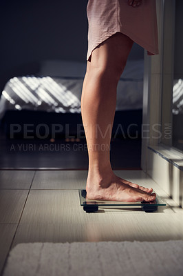Buy stock photo Shot of an unrecognizble woman weighing herself on a scale at home