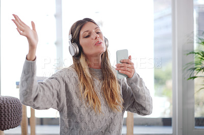 Buy stock photo Shot of an attractive woman using her cellphone while relaxing at home
