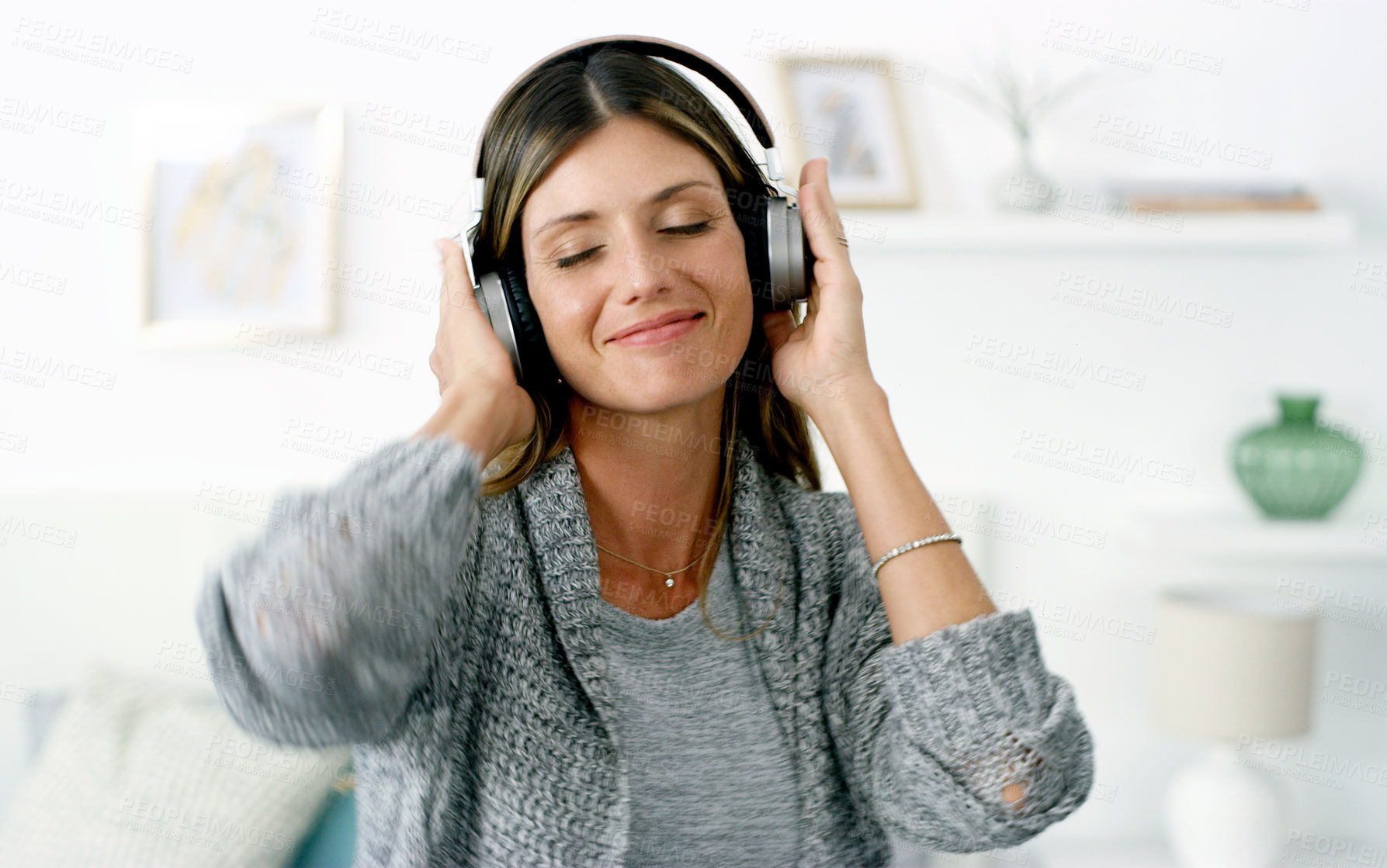 Buy stock photo Shot of a woman listening to music while relaxing at home