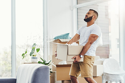 Buy stock photo Shot of a young man carrying a heavy box while moving house