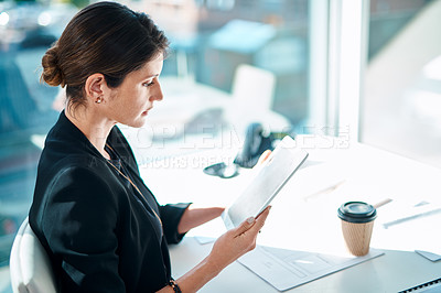 Buy stock photo Shot of a businesswoman using a digital tablet at her desk in a modern office