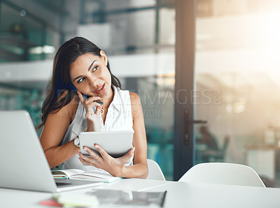 Buy stock photo Shot of a young businesswoman talking on a cellphone while using a digital tablet in an office