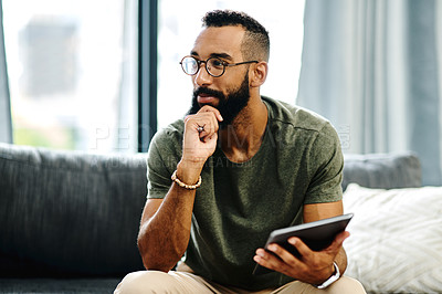 Buy stock photo Cropped shot of a young man using a digital tablet at home