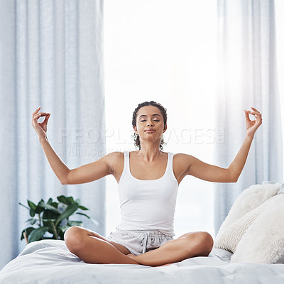 Buy stock photo Shot of an attractive young woman meditating while sitting on her bed in the morning