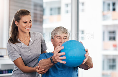 Buy stock photo Shot of a senior man using a ball during a consultation with a physiotherapist