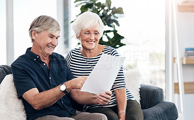 Buy stock photo Shot of a senior couple going through their paperwork together at home