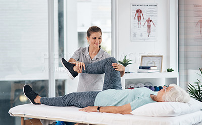 Buy stock photo Shot of a senior woman being treated by a physiotherapist