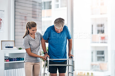 Buy stock photo Shot of a young physiotherapist assisting a senior man with a walker