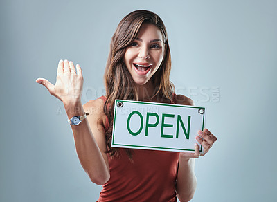 Buy stock photo Studio shot of a young woman holding an open sign against a grey background